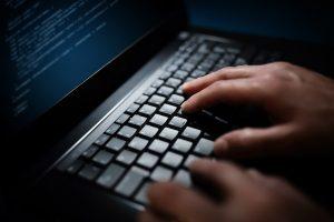 Programmer or computer hacker typing on laptop keyboard